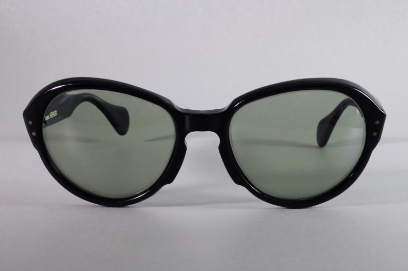 Paire de lunettes d'AUDREY HEPBURN en acétate teinté noir, les verres teintés vert. L'intérieur de la branche droite gravé en lettres blanches : « Audrey Hepburn ». Signée Pierre Marly.
