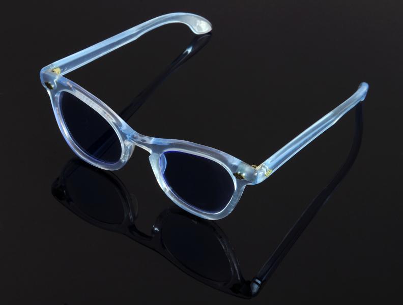 Paire de lunettes de MARLÈNE DIETRICH en acétate teinté bleu pâle, soulignée de rosaces en métal au niveau des charnières.
