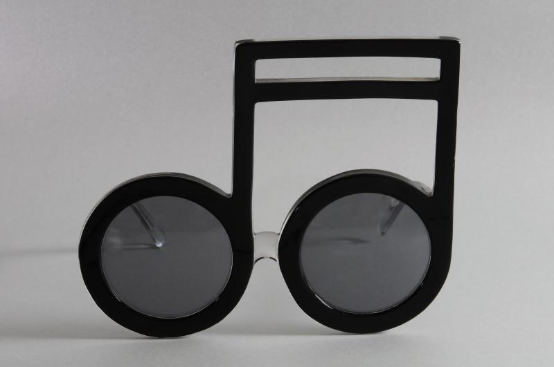 Paire de lunettes d'ELTON JOHN, en forme de notes de musique, en acétate teinté noir, les branches translucides en partie pailletées gris. L'intérieur de la branche droite gravé en lettres blanches : « Elton John ».