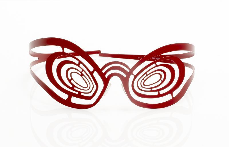 Des anneaux concentriques mettent la porteuse mais aussi le spectateur en un état d'hypnose. Lancée en 1995, la gamme « Eye-witness » (qui propose de nouveaux modèles chaque année) est destinée aux intrépides et aux inconditionnels de la marque.  Eye Withness JR 83, Patrick Hoët (designer), Théo. Acier inoxydable avec découpe au laser, 2002. Don Théo (2009) ©Musée de la Lunette. Photo : Studio Bernardot