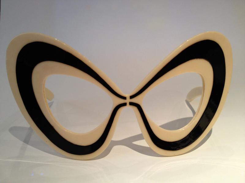 Dès les années 1960, le couturier Pierre Cardin (1922 - ) emprunte au registre de la science-fiction un imaginaire futuriste pour concevoir ses collections. Premier couturier à avoir introduit les matières synthétiques dans ses créations, il crée des vêtements et des accessoires avant-gardistes. Lunette de défilé Pierre Cardin, Forme papillon. Modèle de taille surdimensionnée, acétate de cellulose, vers 1960. Don M. Samuel (2012) ©Musée de la Lunette