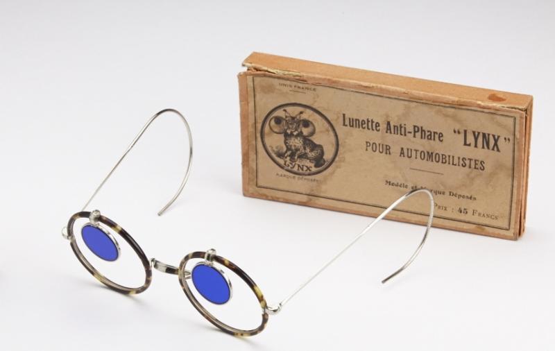 Lunettes anti-phare « Lynx », nitrate de cellulose et maillechort, 1ère  moitié du XXe siècle. Ces lunettes sont pourvues de petits verres amovibles teintés en bleu pour absorber la lumière intense des phares de voiture. ©Musée de la Lunette - coll. Essilor-Pierre Marly. Photo : Pierre Guénat