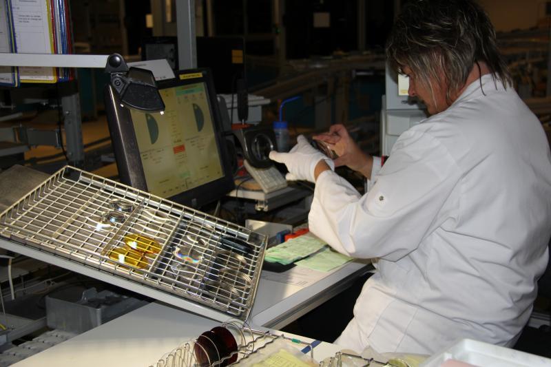 Le contrôle des verres se fait sur 100% de la production. Si la gamme standard va passer par un robot, les verres sur devis sont contrôlés par des opérateurs. En moyenne, 5% des verres sont rejetés et Essilor enregistre 0,4% de retours dus à un problème technique sur le verre. ©Acuité 2014