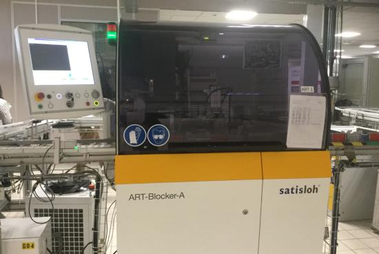 Machine de blocage et de déblocage sans alliage ART développée par Satisloh. La technologie remplace l'utilisation du métal fusible par de la colle UV et permet de s'affranchir du film de protection pour protéger la face avant du verre. Ce procédé de fabrication est moins polluant pour l'environnement