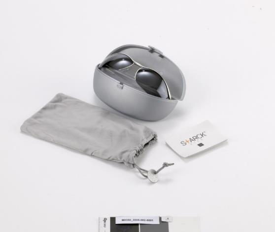 Doté d'une articulation baptisée « biomécanique », fabriquée par Comotec, la charnière s'inspire d'une clavicule humaine et confère à la branche une amplitude de mouvement multidirectionnelle.  Starck Eyes, Modèle Biospeed P0104-03, Philippe Starck, cercles en nylon, manchon en acétate de cellulose, barre frontale en maillechort, finition en aluminium mat, verre en polycarbonate, 1996 – 2002. Don
