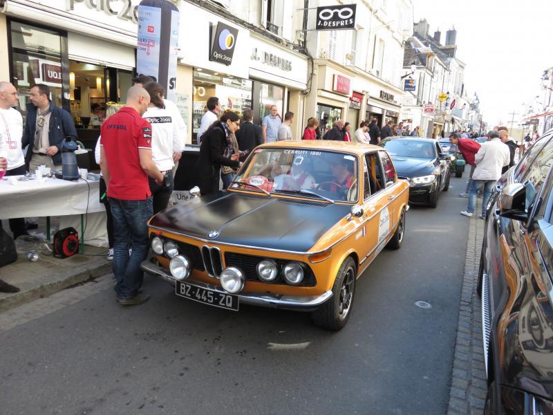 La BMW 2002 Tii pilotée par Philippe Roche est devant un point de contrôle d'un magasin Optic 2000